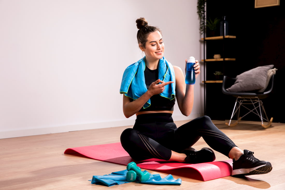 mujer joven bebiendo mientras hace deporte