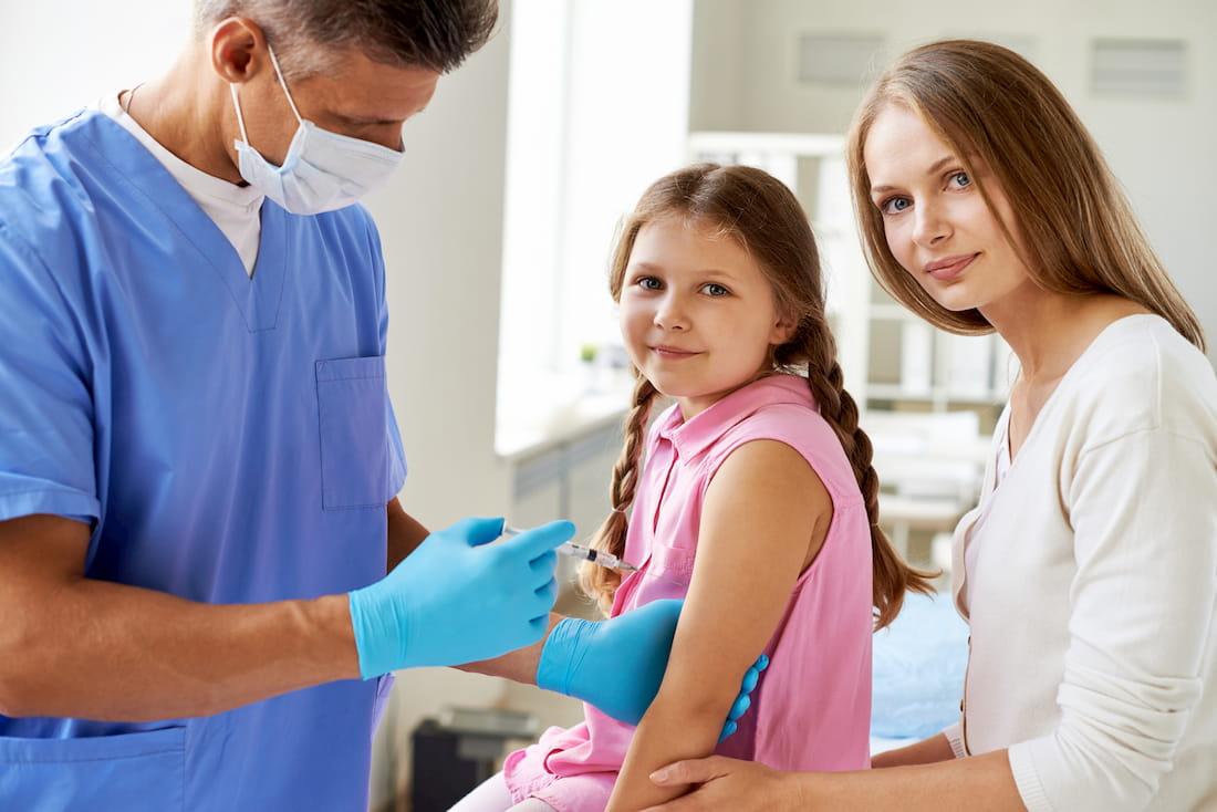 niña vacunándose con su madre y un doctor